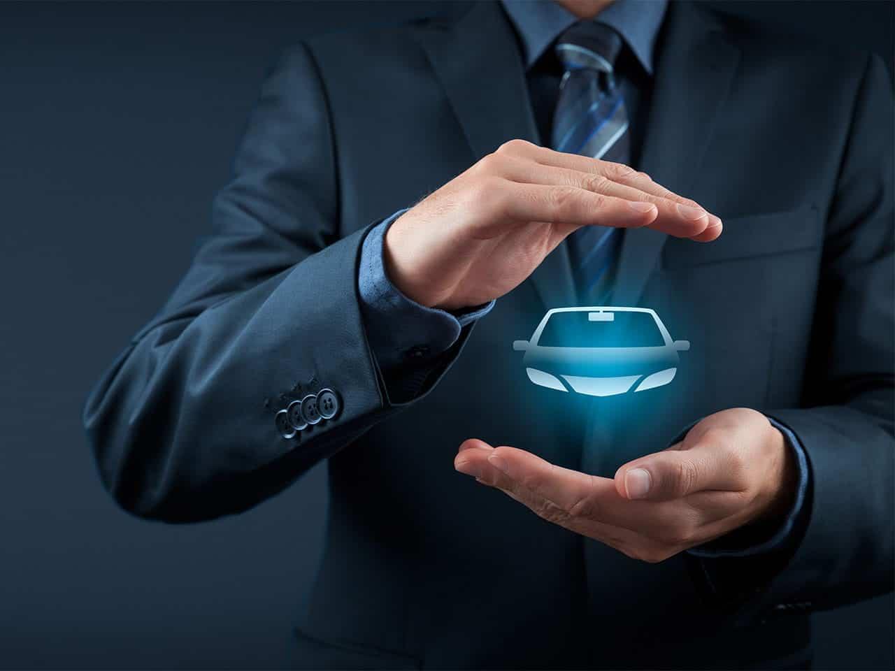 Mann mit einem Auto-Icon in den Haenden.